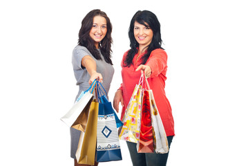 Two women offering shopping bags