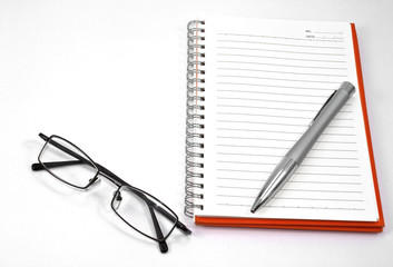 orange notebook and eyeglasses
