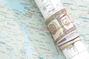 Rolled saudi arabian money in a blueprint