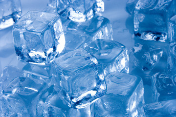 Frozen ice cubes on blue background