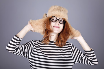 Funny girl in winter cap and glasses.
