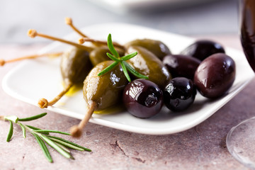 Caper berries and black olives on a stone background