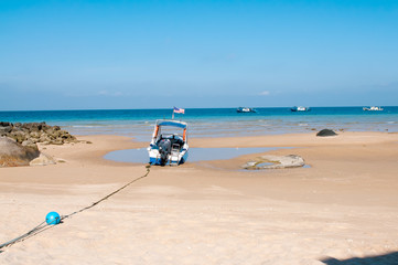 Scenery of the small boat at the beach with blue sky