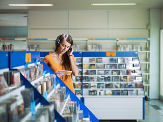 Tuinposter Muziekwinkel girl listening music in cd store