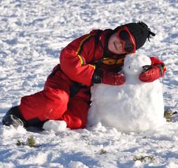 sport d'hiver jeune garçon heureux avec son bonhomme de neige
