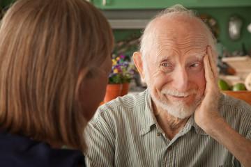 Senior couple at home focusing on man