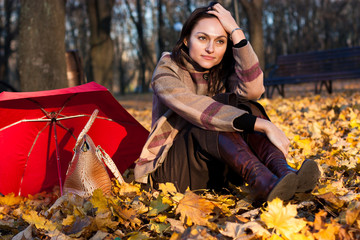 Beautiful young woman sitting in autumn leaves