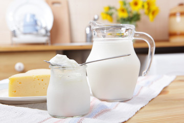 Yogurt, yellow cheese, and the jug of milk on a kitchen table