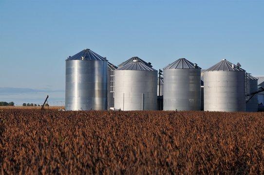 Steel silos in a grassy field in rural