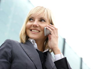 A young and happy blond businesswoman on the phone