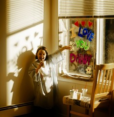 Little Girl Painting 'i Love You Daddy' On Window