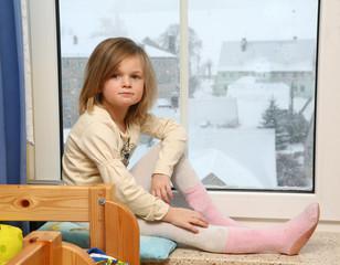 junges Mädchen sitzt am Fenster
