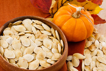 Pumpkin seeds and pumpkin against colorful autumn accents