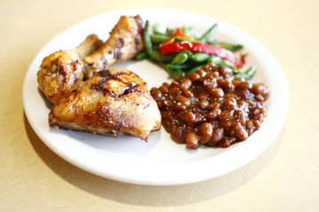 Baked chicken with a side of baked beans and peas