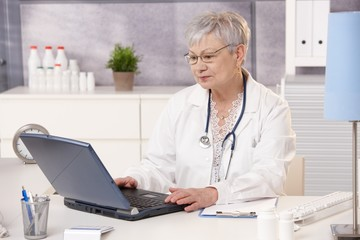 Senior doctor working at desk