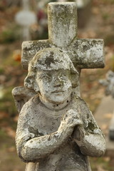 antique sculpture of child praying on cemetery