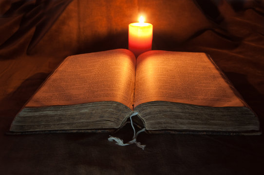 Bible lighted by a Candle