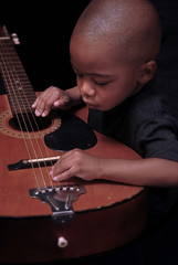 little boy plays the guitar