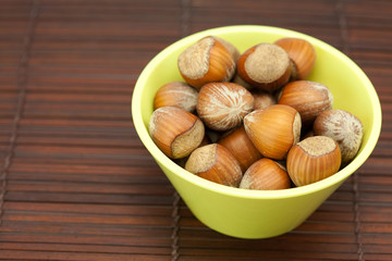hazelnuts in a bowl on a bamboo mat