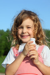 little girl with a yoghurt small bottle, against wood