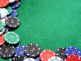 Poker chips on a green felt background with copy space
