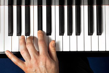 hand on piano with reflection 2