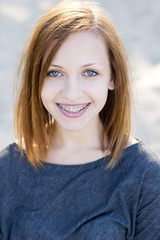 Charming teenage girl wearing braces and smiling cheerfully