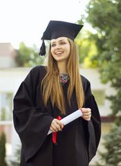 A graduate holding a diploma and looks toward
