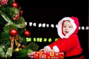 Baby in Santa costume over black