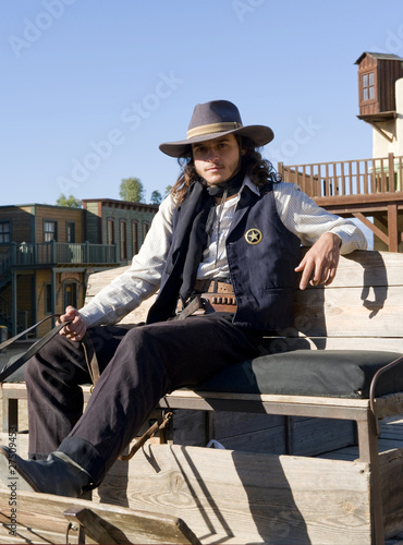 Wall mural Sheriff sitting on a wagon on a film set