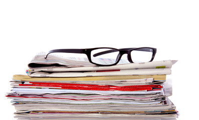 reading glasses on a pile of newspapers isolated over white