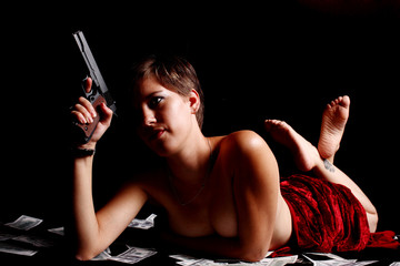 Sexy woman wrapped in red satin and holding a pistol