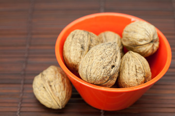 walnuts in a bowl on a bamboo mat