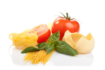 Pasta, tomato and basil leaves on white background