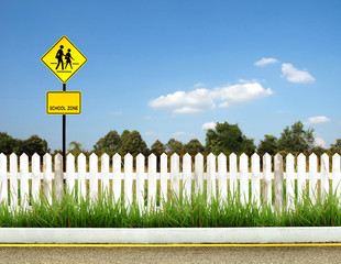 school zone sign with white fence and blue sky