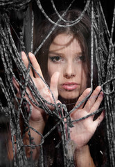 portrait of young girl looking through wet window and textile ne