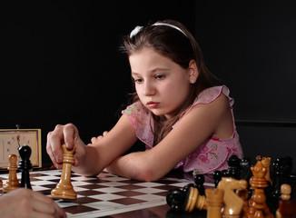 Teenage girl 12-13 years old playing chess. Check