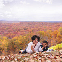 Scenic fall portrait of grandma and toddler grandchild