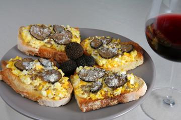 Pane tostato con uova strapazzate e tartufi neri (sfondo chiaro)