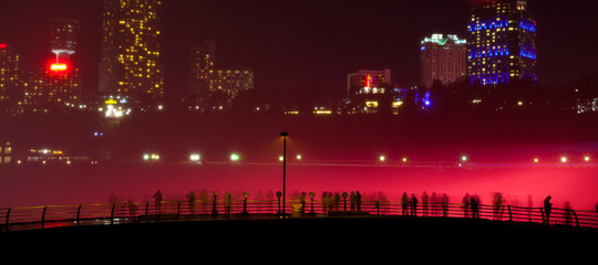 The tourist near the niagara waterfalls in the red night light