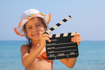 girl standing on beach and holding clapboard. focus on girl eyes
