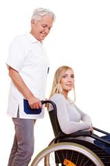 Krankenschwester schiebt Rollstuhlfahrerin