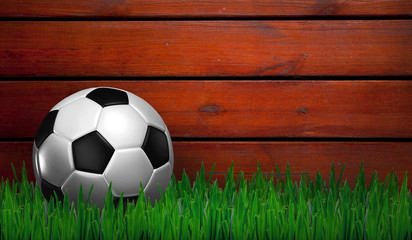 football on grass with wood background