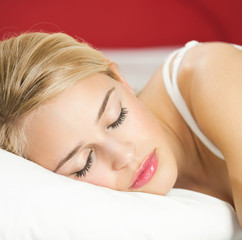 Young attractive blond woman sleeping on bed
