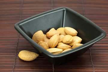 almonds in a bowl on a bamboo mat
