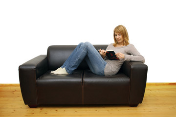 woman lying on a sofa and reading a book