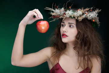 studio shot of young beautiful woman with apple