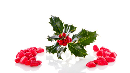 a christmas holly branch between decorative stones isolated over