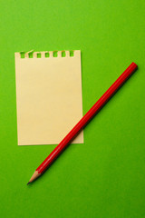 Sheet and pencil isolated on green