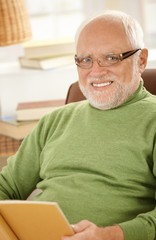 Portrait of smiling senior man with book